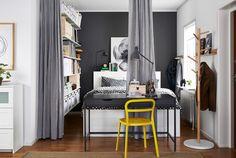 BRIMNES Bettgestell mit Schubladen in Weiß in einer großen Schlafecke, davor ein geöffneter Raumteiler aus Stoff von IKEA.