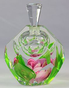 'Kosta Paperweight Perfume Bottle' [Designed by *Swedish glass master* ~Jan-Erik Ritzman~] [The beauty of the bottle resides in the enclosed pink flower at its base which is surrounded by wisps of green simulating leaves. The bottle is well complemented by a clear cut hexagonal stopper. 5 1/4 inches tall.] [Jan-Erik Ritzman began working at the Kosta Boda factory in 1957. He was the first European Glass Master to demonstrate glassblowing in the United States.]