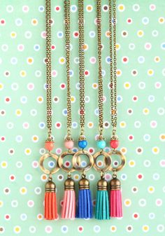 A really fun, versatile, bohemian style necklace featuring a suede tassel attached to a circular, hammered antique brass connector. Above the circle is a glass bead in a similar color to the suede tassel. By Jacarandadesigns