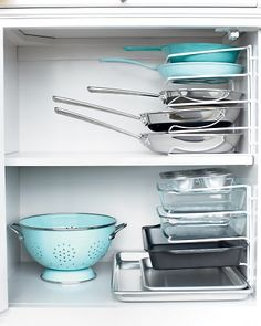 Turn vertical bakeware organizer on its end to stack pots & pans instead of nesting them. Secure it to the cabinet wall with cable clips to prevent toppling.