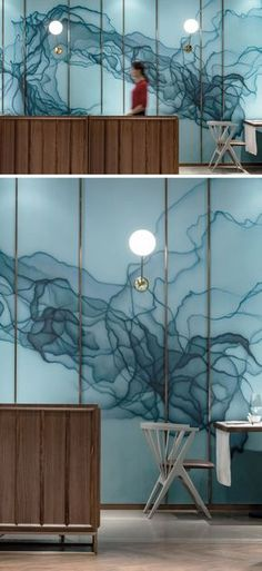 In this modern restaurant, there's an artistic wall that features an ink and dye pattern in shades of blue on embossed glass. #AccentWall #Blue #ModernRestaurant