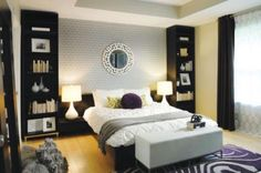 Master Bedroom Interior Design. Purple and white rug. Black shelves and night stands. White brick wall, Mirror over bed.