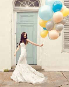 Cute photo idea, kind of whimsical. I like the pop of colour the balloons give against the white of the gown.