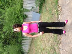 Pink shirt, pink flats, black pants, animal print belt with black buckle and black earrings