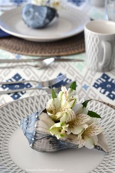 Whelk shell as vase for alstroemeria blooms and Mikasa Aurora Grey dinnerware   homeiswheretheboatis.net #tablescape