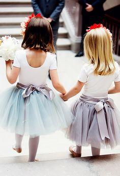 Two flower girls wearing pastel coloured tutus