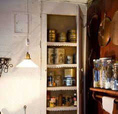 OPPBEVARING: Skapet ved vedovnen har fått hylleremser som Bertils søster har laget. Her oppbevares blant annet kaffe og te i små, fine bokser.