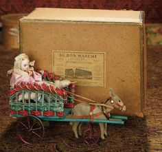 """10"""" All-Original French Mechanical Toy """"Little Girl in Cart"""" with Nodding Head Donkey~~~The cart is being pulled by a paper mache donkey with black bead eyes, nodding attached head, leather harness, and one small wheel beneath. When wound, the cart moves forward, and the little girl moves her body back and forth as though urging the nodding head donkey forward.  attributed to Vichy, circa 1880. Value Points: the enchanting toy is perfectly preserved, stored in original box from Au Bon Marche"""