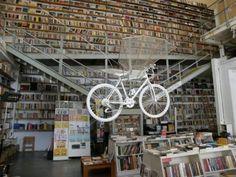 """IlPost - Lisbona, Portogallo - Ler Devagar (che in portoghese vuol dire """"leggere con lentezza"""") ha una bicicletta volante e libri fino al soffitto (dalla pagina Facebook della libreria)"""