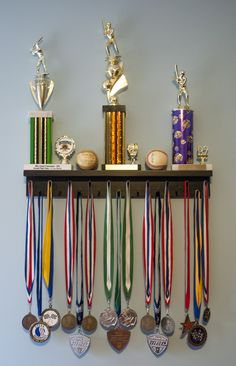 "Ships in 1-3 Business Days!! 19 pegs to accommodate lanyard ribbon medals Dual Groove shelf design to accommodate up to 9 pin style cased medals 2 1/2"" wide top shelf for the placement of trophies, plaques or other accolades Product includes 2 screws for mounting and mounting instructions US"