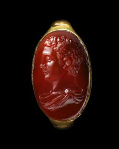 Gold ring, the long oval bezel set with a cornelian intaglio bust of Mercury, with a wing in his curly hair, neckline draped, facing in profile towards the left. Ring and intaglio Roman, 1st century A.D