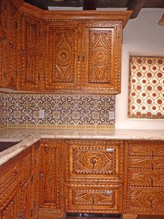 Carved Custom Cabinets kitchen in vintage adobe that called for Spanish Colonial Revival Style in Santa Fe, New Mexico.