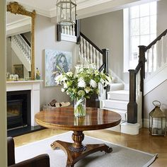High ceilings and dark wood banisters add grandeur to this traditional hallway. Distressed French-style antiques, glassware and furniture creates an elegant feel.