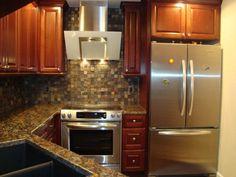 tiled backspash, custom stainless rangehood, cabinets, granite countertop, stainless range and fridge