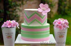 Torta con diseños simétricos, chevron y rayas horizontales, en rosa y verde pastel.   Green and pink pastel cake, with chevron design and stripes.