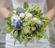 This bouquet created of fresh green mixed foliages like salal, sword fern, eucalyptus and varigated mini pittosporum is clustered with white spray roses, bells or ireland and a touch of blue delphiuium to bring out the color of the brides shoes.