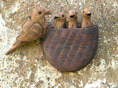Hnízdo ptačí Ručně vytvořené hnízdo s mladými nenasytnými ptáčky a obětavým rodičem. Na zadní straně dva otvory pro hřebíky či hmoždinky. Páleno na 1150 st. glazováno, zatřeny oxidy. Velikost 15 cm x 18 cm
