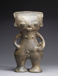 Pre-Columbian Standing Figure of a Mother and Child, AD 500-1550, made of brown-gray terracotta.Looks like a outer space figure.