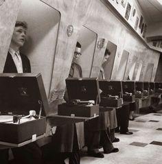 Clientes de uma loja de música ouvindo os últimos lançamentos em uma cabine à prova de som, 1955