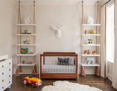 Chic boy's nursery boasts a wall clad in light gray faux bois wallpaper by Schumacher lined with a resin stag head placed above a wood and acrylic crib, Spot on Square Roh Crib, flanked by rope hung bookshelves suspended by the ceiling.
