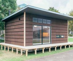 Jasper Morrison's Muji Hut clad in cork with a timber deck and gently sloping roof.