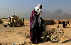 FILE PHOTO: A woman who is fleeing the fighting between Islamic State and the Iraqi army in the Intisar district of eastern Mosul, walks past a military humvee while heading to safer territory in Iraq November 7, 2016. REUTERS/Zohra Bensemra/File Photo