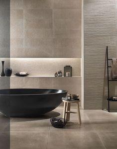 salle de bain ambiance zen avec une baignoire îlot noire ovale et un carrelage effet pierre beige