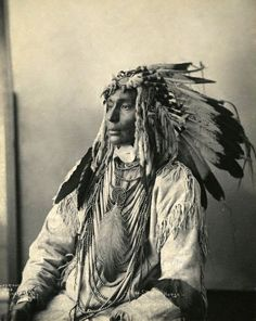 This Nakoda (Assiniboine) warrior wears a feathered bonnet made from the tail feathers of eagles. These headdresses were traditionally worn by the most prominent men of the Plains. Photographed by Frank A. Rinehart, 1898.