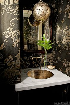 Powder Room That Pack A Punch. Fans of the dramatic should take note of this black and gold space.