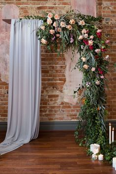 Romantic ceremony arbour draped with blue fabric and pink floral garland in industrial wedding venue   Anna Pretorius Photography & The Stache Photography