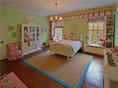 Cute kids bedroom with green color walls and hardwood floors.