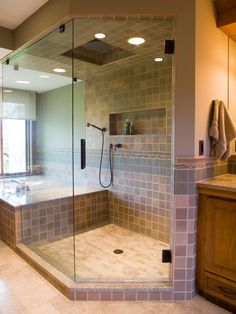 This master bathroom features a custom-designed shower with a frameless enclosure, built-in niche, 12-inch rain showerhead and oil-rubbed-bronze hardware. The neutral tiling in the space is stylish yet timeless.