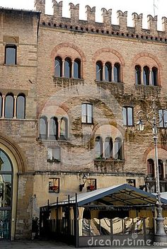 Photo made in Parma (Italy). The picture shows the crenellated facade of an old medieval building in the city center. I am very particular the triple six arched windows with two slender white columns.