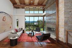 grand tableau abstrait, tapis rouge, parement en pierre et chaises Barcelone
