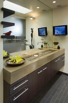 An alternative to double sinks: trough sink with two wall-mounted faucets. Love the metal overlay to hold a glass of water or wine. It's sleek, a space-saver, requires less cleaning and only one drain.