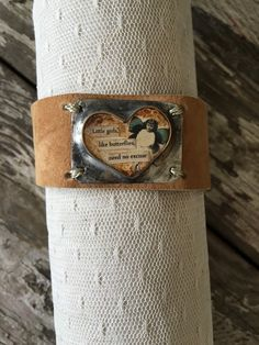 "This is a beautiful handcrafted Leather cuff with a heart soldered bezel. I have handpainted inside the bezel and added a little fairy with teal wings. I also added the words ""Little girls, like butterflies need no excuse"". This cuff will fit wrists up to 8"" and will adjust down to a 7"". I hand make every one of these Cuffs and no two will ever be the same. Each piece is an original <3 <3 <3 This listing is for one cuff."