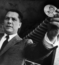 """Jimmy Hoffa holds a """"Hoffa for President"""" button during his 1959 campaign for the Presidency of the Teamsters Union."""