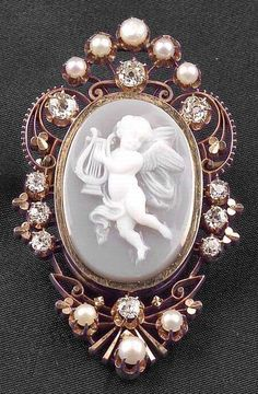 Antique 14kt Gold Hardstone Cameo, Diamond and Seed Pearl Pendant/Brooch, carved to depict a cherub playing a lyre, framed by old European-cut diamond melee and seed pearls.
