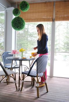 Lighted boxwood pendants hang over an outdoor dining set