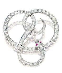 Platinum topped gold and diamond serpent brooch, circa 1910. The intertwined serpent signifying love, set with old European-cut diamonds weighing approximately 5.15 carats, the eyes set with round rubies. [Tone, color and contrast has been *very* slightly altered in order to better see the design]