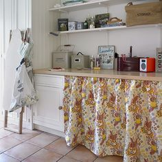 Laundry room. To soften the look of a designated laundry area, conceal appliances behind a simple gathered curtain in a chic 1950s-style pattern. Maximise utility room storage with tall cupboards as well as base cabinets. Open shelving on brackets and a pale wood worktop can take supplies. Use them for vintage containers filled with everyday detergents, linen sprays and beautifully packaged items.  Similar fabric, St Judes, Similar ironing board, Garden Trading.