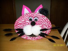 Homemade Valentine's Day Card Box! I bought an oval shaped box from Hobby Lobby, glued fabric on the box, cut a mouth to put cards into, cut the ears out of foam sheets, added pom poms, pipe cleaners, goggle eyes and the final touches of fake eye lashes and a clip in black flower! Tons of fun and so cute!