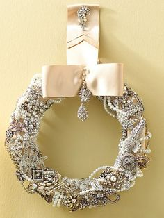 vintage sparkle wreath: wrap a foam wreath with cream color satin ribbon: pin in place to secure. hot glue or pin pearls and fake jewels from crafts store onto ribbon. wind strands of pearls over secured pieces of jewelry. tie a satin bow to hang wreath and garnish with more bling!   I like the wreath....not to sure about the ribbon/bow thing.