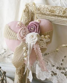 Závěsné srdíčko Shabby chic Závěsná dekorace - srdíčko v úpletu ve stylu Shabby chic Zdobení ručně vinutými růžičkami každá s perličkou abavlněná krajka. Jako závěs je bižuterní zlatý řetízek s perličkou. Barvy starorůžová, krémová,bílá. Průměr 10 cm.