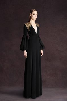 Black velvet gown with opulent layered gold beading on shoulders and modified lantern sleeves. Andrew Gn 2013.