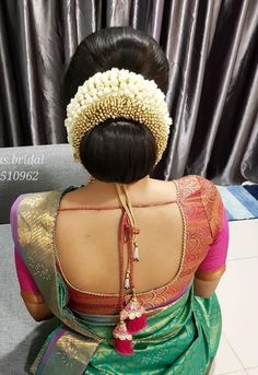 What a beautiful large low bun with real flower gajra! Care however should be taken before adopting such hairstyles, as due to it's high static charge, it will cause phlegm to move up in the throat, causing the voice to quaver & a frequent urge to clear the throat. A heavy chabi chhalla with a long & wide hook if inserted at the edge of the pleats of the saree, will reduce this problem as it's hook will activate the acupressure points that act to keep the throat clear. Bridal Hairstyle Indian Wedding, South Indian Bride Hairstyle, Bridal Hair Buns, Bridal Hairdo, Indian Wedding Hairstyles, Saree Hairstyles, Bride Hairstyles, Hairdos, Hairstyles Haircuts