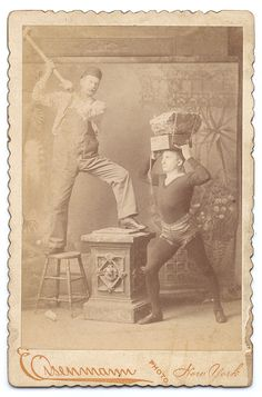 Impressive sideshow cabinet card of a man dressed in bib overalls and wearing a fez-style hat, swinging a sledgehammer towards Billy Wells, a human blockhead with two large stones strapped to his head.