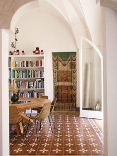 Uma casa antiga com decoração atual. Mesa de jantar redonda de madeira com vaso plantas, estante de livros e luz natural.  #decoracao #decor #casadevalentina