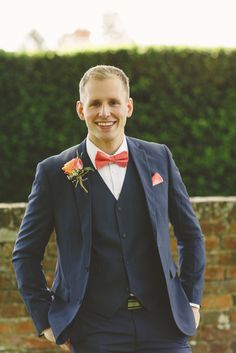 A smart navy 3 piece suit and brightly coloured bow tie for the groom. Photo by Benjamin Stuart Photography #groom #suit #wedding