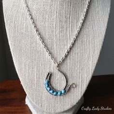 Silvertone horseshoe necklace with turquoise colored beads